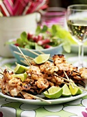 Grilled prawn skewers with lime wedges on plate