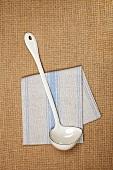 Enamel ladle on a tea towel