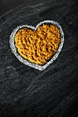 Curry powder in a heart drawn in chalk on a slate