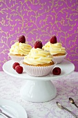 Cupcakes with buttercream and raspberries on cake stand