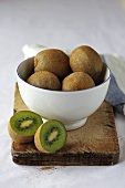 Whole and halved kiwi fruit in and beside bowl on wooden board