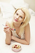A young woman eating muesli in bed