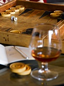 Glass of brandy in front of backgammon board