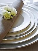Gepunktete Teller und Stoffserviette mit weissen Rosen