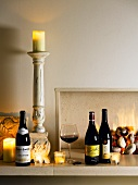 Bottles of red wine, glass of wine and candles in front of fire