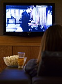 Woman with beer and popcorn in front of TV