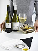 Woman serving tray of white wine and oysters