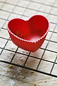 Red heart-shaped silicone baking mould on cake rack
