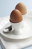 Two boiled eggs in egg cups with spoon on plate