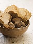 Fresh potatoes in torn paper bag in bowl