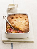Rhubarb pudding in baking dish, jug of cream