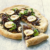Pizza topped with red onions and goat's cheese, a piece cut
