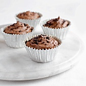 Four chocolate cupcakes on marble plate
