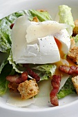 Caesar salad with poached egg, bacon and croutons