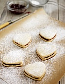 Heart-shaped jam sandwich biscuits on baking parchment