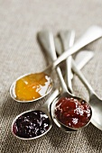 Spoonfuls of apricot, raspberry and blackberry jam