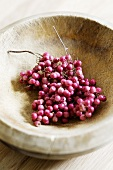 Pink peppercorns in wooden bowl