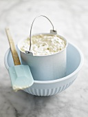 Home-made ice cream in container in bowl with spatula