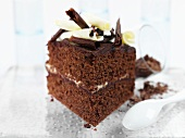 Square of chocolate cake with chocolate curls