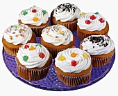 A variety of decorated cupcakes on a glass plate
