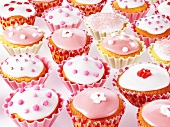 Lots of fairy cakes decorated in pink and white
