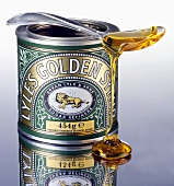 Golden syrup trickling off a spoon