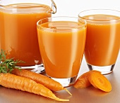 Carrot juice in glasses and a glass jug