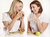 Zwei Frauen essen Sandwiches und trinken Wasser