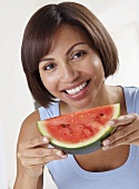 A woman holding a slice of watermelon