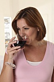 A woman drinking a glass of red wine