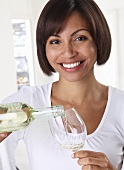 A woman pouring white wine from a bottle into a glass