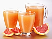 Pink grapefruit juice in glasses and a glass jug