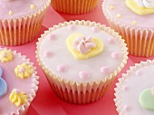 Pastel-coloured fairy cakes decorated with sugar flowers