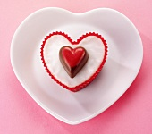 A heart-shaped fairy cake decorated with a heart-shaped praline