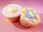 Fairy cakes with pink icing, heart-shaped decorations and sugar flowers