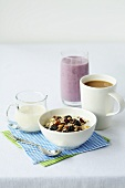 Muesli, a blueberry smoothie, a cup of tea and milk