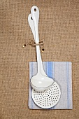 An enamel ladle and a slotted spoon on a dish cloth