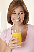 A smiling woman holding a glass of orange juice