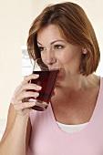 Frau trinkt ein Glas Fruchtsaft