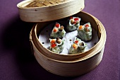 Stuffed dough parcels with mushroom and vegetables in a bamboo steamer