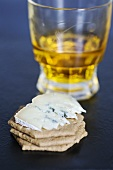 Blue cheese (type: Mrs Temple's Binham Blue, Norfolk, UK) on crackers with a glass of whiskey