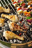 Chicken legs and vegetable kebabs on a barbeque