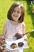 A girl holding a plate of grilled meatballs