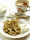 Baked elderflowers with cream and a cup of tea