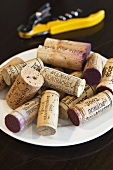 Various wine corks on a plate with a cork screw in the background