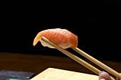 A hand holding a nigiri sushi in chopsticks