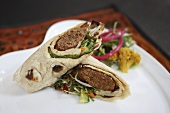 A wrap filled with sausage and salad