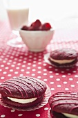 Raspberry whoopie pies on a spotted tablecloth with fresh raspberries and a glass of milk