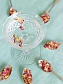 Rosenwasser mit getrockneten Rosenblättern in einer Glasschale