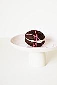 Schokoladen-Whoopie Pie, mit Schnur umwickelt, auf Kuchenständer